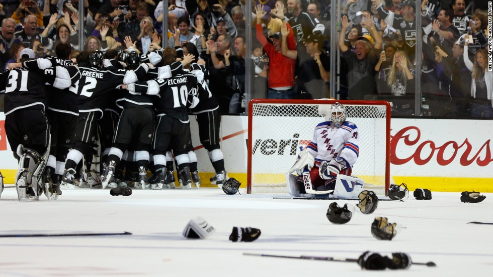 The Los Angeles Kings celebrate their Stanley Cup victory as New York Rangers goaltender Henrik Lundqvist kneels in the crease Friday, June 13, in Los Angeles.