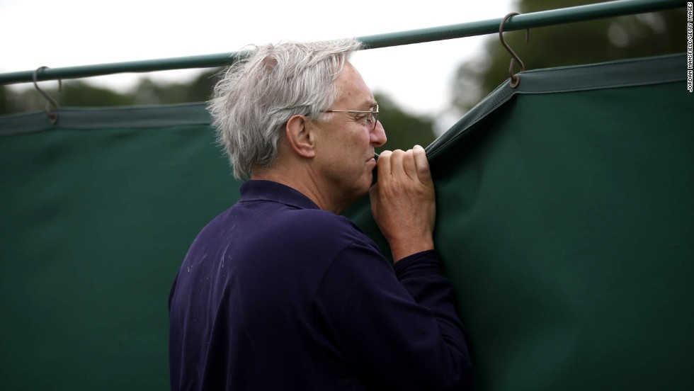 A man peers over a fence to watch Wimbledon qualifying matches Monday, June 16, in London. The tennis tournament begins Monday, June 23.