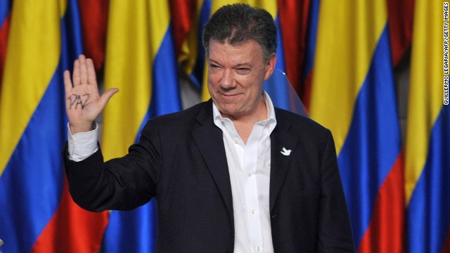 "Colombian President and presidential candidate Juan Manuel Santos shows the palm of his hand reading ""Peace"" as he celebrates after knowing the results of the runoff presidential election on June 15, 2014, in Bogota. Santos was re-elected with 50.90 percent of the vote, compared with 45.04 percent for the more conservative Oscar Ivan Zuluaga, with 99.37 percent of votes tallied."