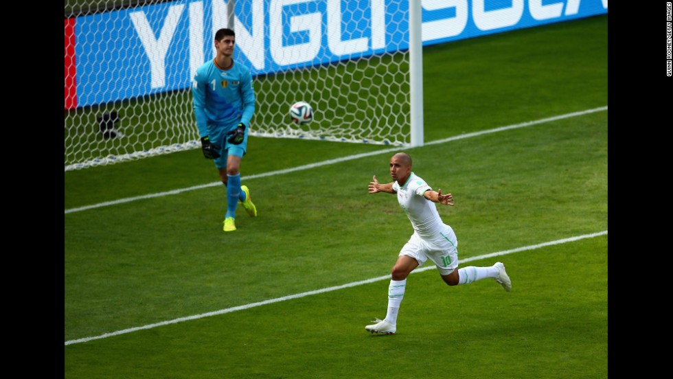 Feghouli runs to the corner of the field after his penalty kick beat Belgian goalkeeper Thibaut Courtois.