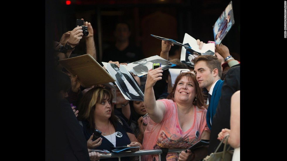 "Actor Robert Pattinson poses with a fan at the premiere of ""The Rover"" on Thursday, June 12, in Los Angeles."