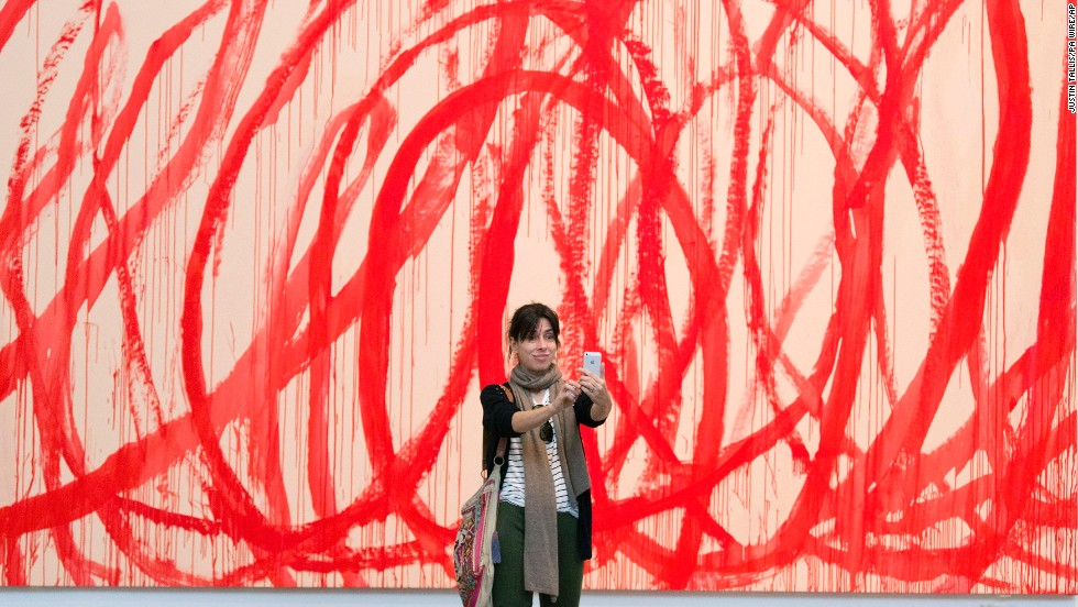 A woman snaps a selfie in front of a Cy Twombly painting Wednesday, June 11, at the Tate Modern museum in London.