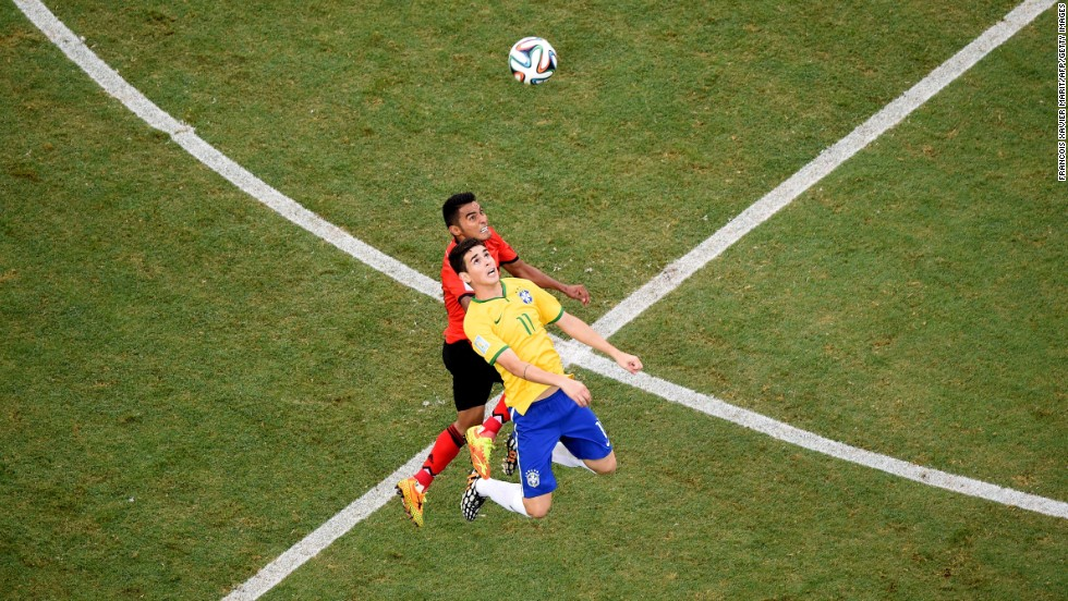 Mexican midfielder Jose Juan Vazquez, left, competes for the ball with Brazil's Oscar.