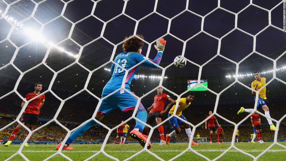 Ochoa makes a save after a header by Brazil's Thiago Silva, right.