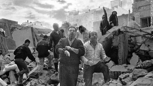 Firemen search as wounded people walk over the rubble left after a bomb exploded at the Argentinian Israelite Mutual Association (AMIA in Spanish) in Buenos Aires, 18 July 1994.