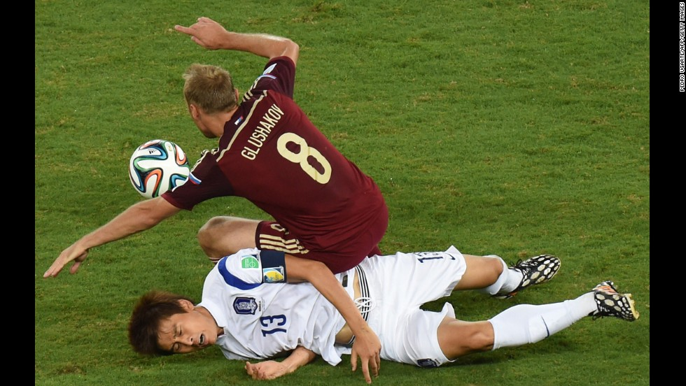 South Korean forward Koo Ja-Cheol, bottom, vies with Russian midfielder Denis Glushakov.