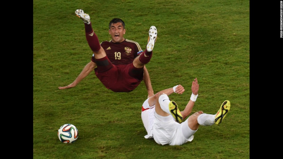 Russian forward Alexander Samedov, left, and South Korean midfielder Ki Sung-Yueng fall during the game.