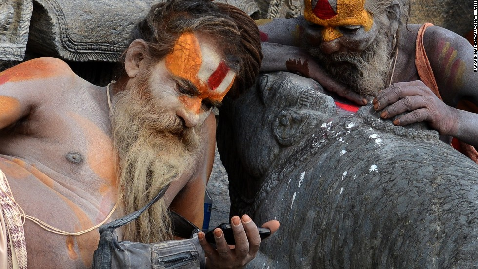 JUNE 18 - KATHMANDU, NEPAL: Hindu sadhus -- holy men -- watch a film on a mobile phone at the Pashupatinath Temple on June 17. Dozens of sadhus live around the temple devoting their lives to Lord Shiva - the Hindu god of destruction.