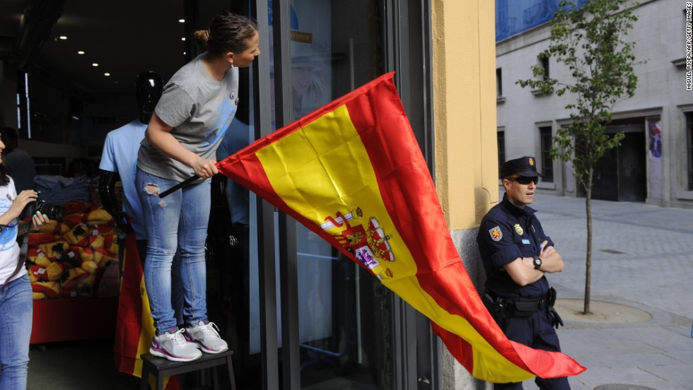 Store attendants put up Spanish flags in Madrid.