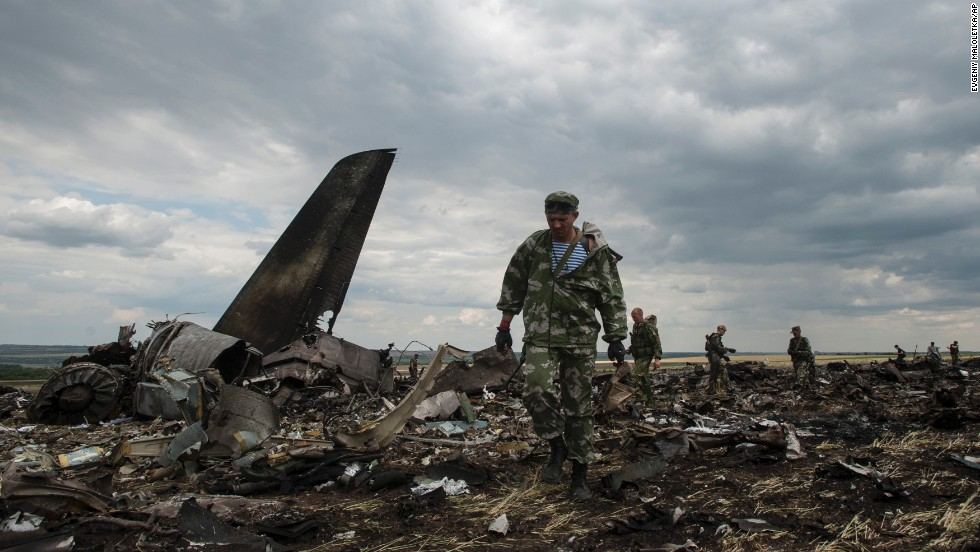 "Pro-Russian fighters walk at the site of a <a href=""http://www.cnn.com/2014/05/27/world/gallery/ukraine-after-election/index.html"">downed Ukrainian army aircraft</a> near Luhansk, Ukraine, on Saturday, June 14. Ukraine's defense ministry said the plane was shot down by insurgents using anti-aircraft machine guns. All 49 people aboard were killed."