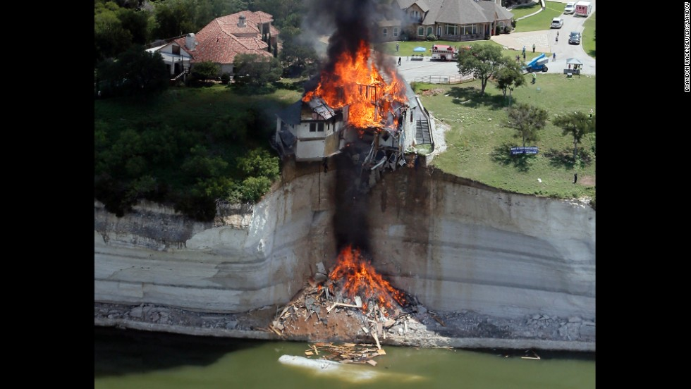 Smoke rises from a house that was deliberately set on fire by building crews Friday, June 13, days after part of the ground underneath the home collapsed into Lake Whitney in Texas.