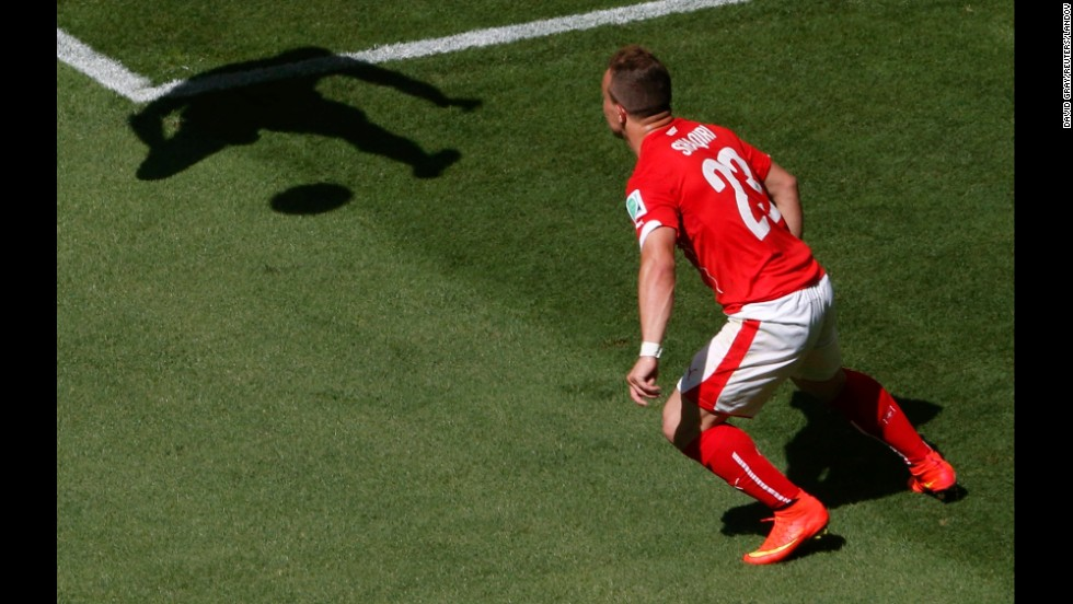 Switzerland's Xherdan Shaqiri looks at the shadow of Ecuador's Walter Ayovi during a World Cup match Saturday, June 14, in Brasilia, Brazil. Switzerland won the match 2-1 on a last-gasp goal by Haris Seferovic.