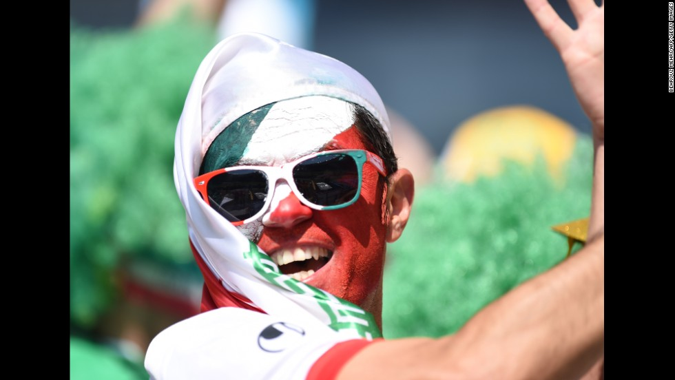 A fan painted with the Iranian colors poses before the match.