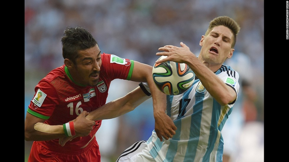 Iran forward Reza Ghoochannejhad, left and Argentina defender Federico Fernandez vie for the ball.