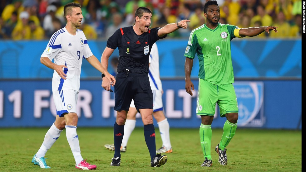 Referee Peter O Leary makes a point to Joseph Yobo of Nigeria and Vedad Ibisevic of Bosnia.