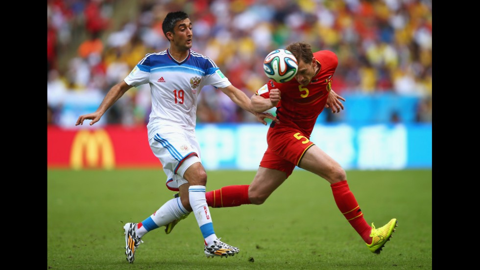 "Jan Vertonghen of Belgium and Alexander Samedov of Russia compete for the ball. <a href=""http://www.cnn.com/2014/06/21/football/gallery/world-cup-0621/index.html"">See the best World Cup photos from June 21.</a>"