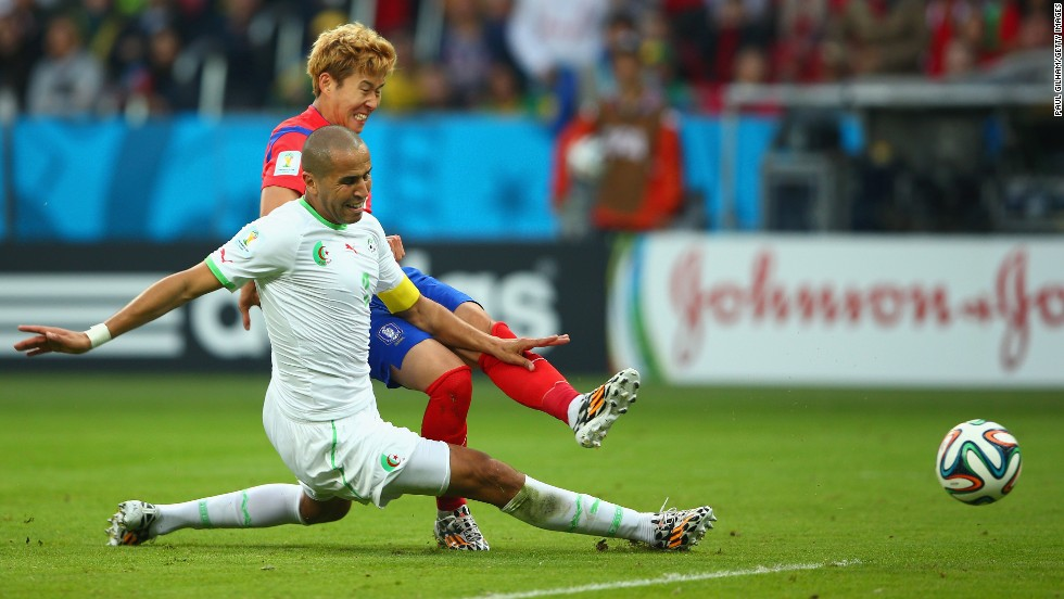 Son Heung-min of South Korea scores his team's first goal past Madjid Bougherra of Algeria.