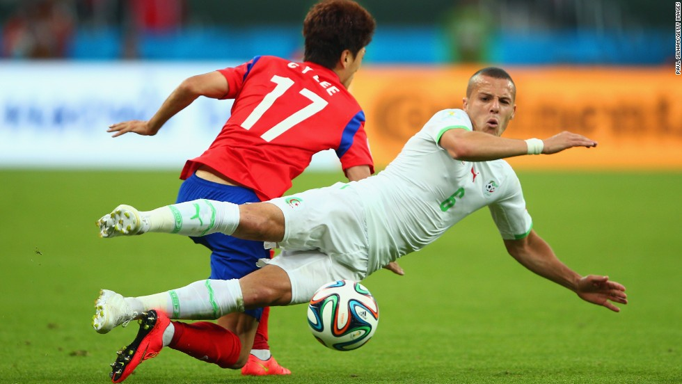 Djamel Mesbah of Algeria vies for the ball with Lee Chung-yong of South Korea.