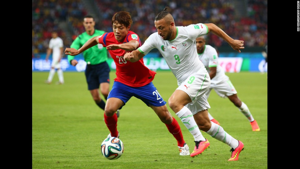Hong Jeong-ho of South Korea and Nabil Ghilas of Algeria compete for the ball.