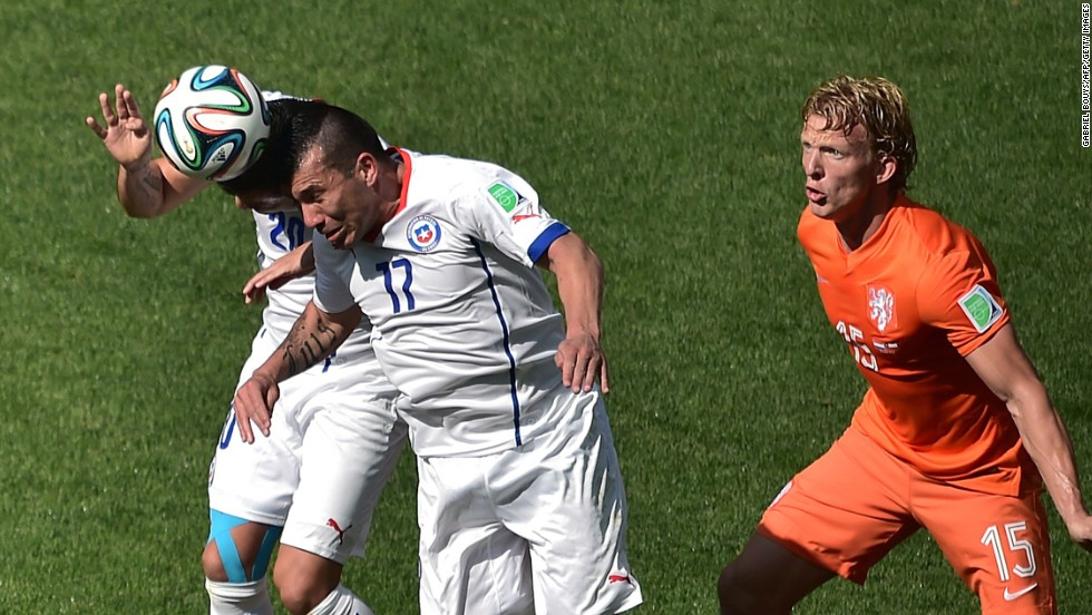 Chile defender Gary Medel, center, heads the ball next to his teammate Charles Aranguiz, left, and Netherlands forward Dirk Kuyt.