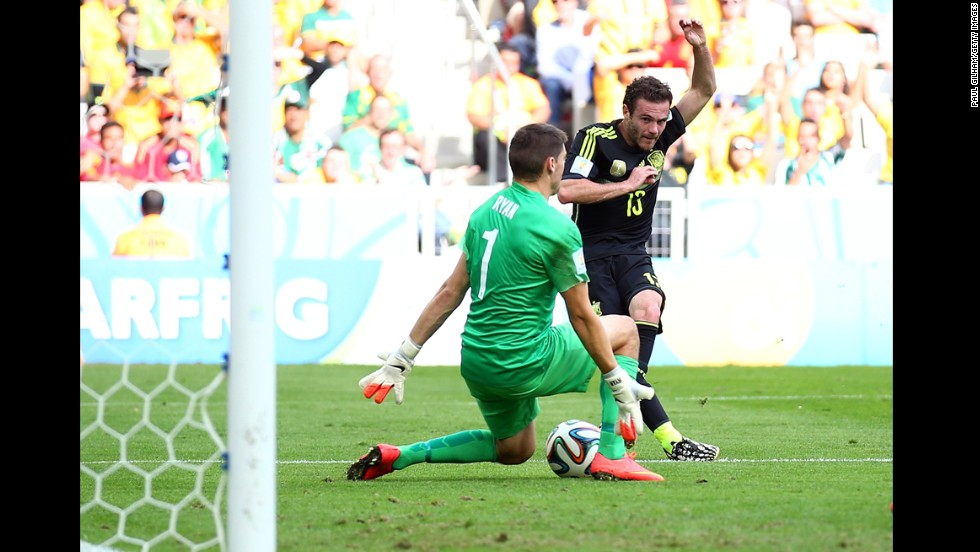 Juan Mata of Spain scores his team's third goal past Mathew Ryan of Australia during a World Cup match in Curitiba, Brazil. Spain won with a final score of 3-0.