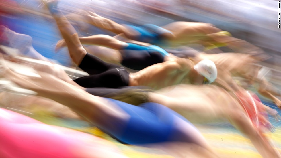 Athletes dive into the water during the men's 50-meter freestyle preliminaries at the 2014 Arena Grand Prix in Santa Clara, California, on Saturday, June 21. The image was captured using a slow shutter speed to create a motion blur effect.