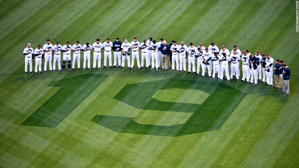"San Diego Padres players and coaches bow their heads during a moment of silence next to a No. 19 painted on the field as a tribute to Tony Gwynn before a game against the Seattle Mariners on Wednesday, June 18, in San Diego. Gwynn, a Hall of Fame outfielder who spent his entire Major League Baseball career with the Padres, <a href=""http://www.cnn.com/2014/06/16/sport/gwynn-baseball-death/index.html"">died earlier in the week</a>. He was 54."
