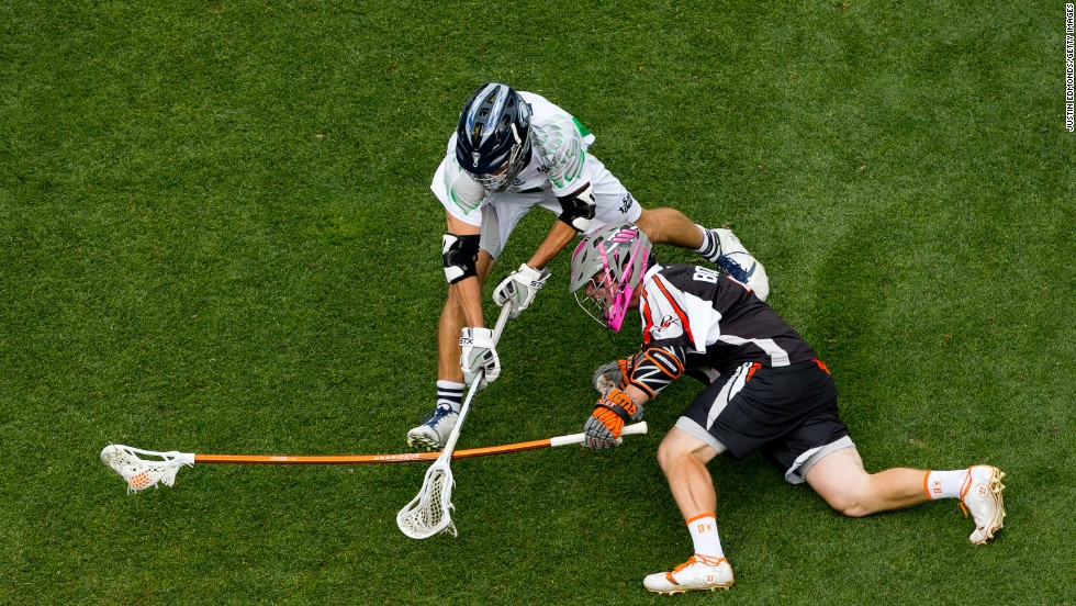 Dan Burns of the Chesapeake Bayhawks tries to knock the ball away from Matt Bocklet of the Denver Outlaws during the third quarter on Saturday, June 21, in Denver. The Outlaws won the lacrosse match 9-6.