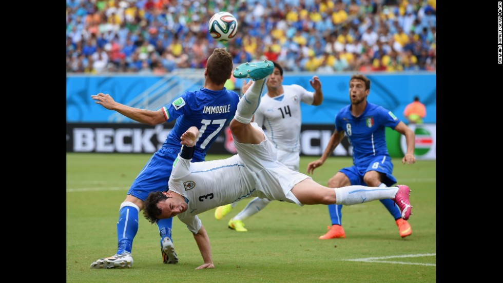 Diego Godin of Uruguay and Ciro Immobile of Italy compete for the ball.