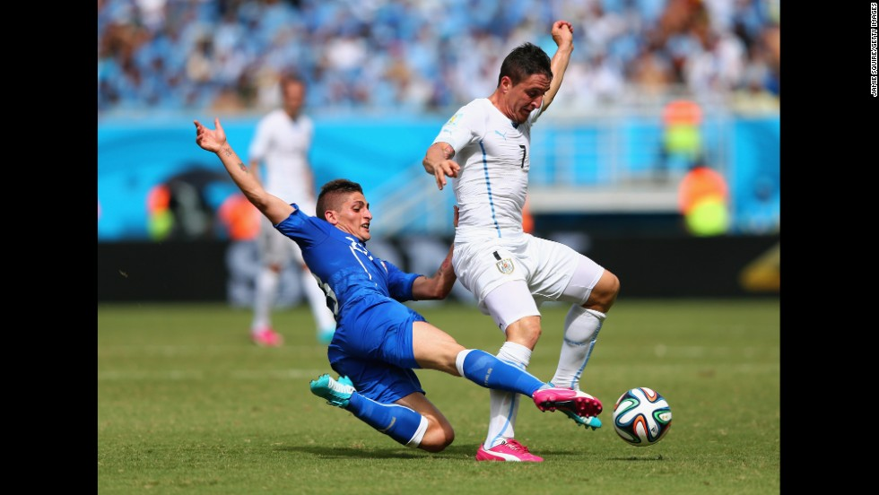 Marco Verratti of Italy tackles Cristian Rodriguez of Uruguay.