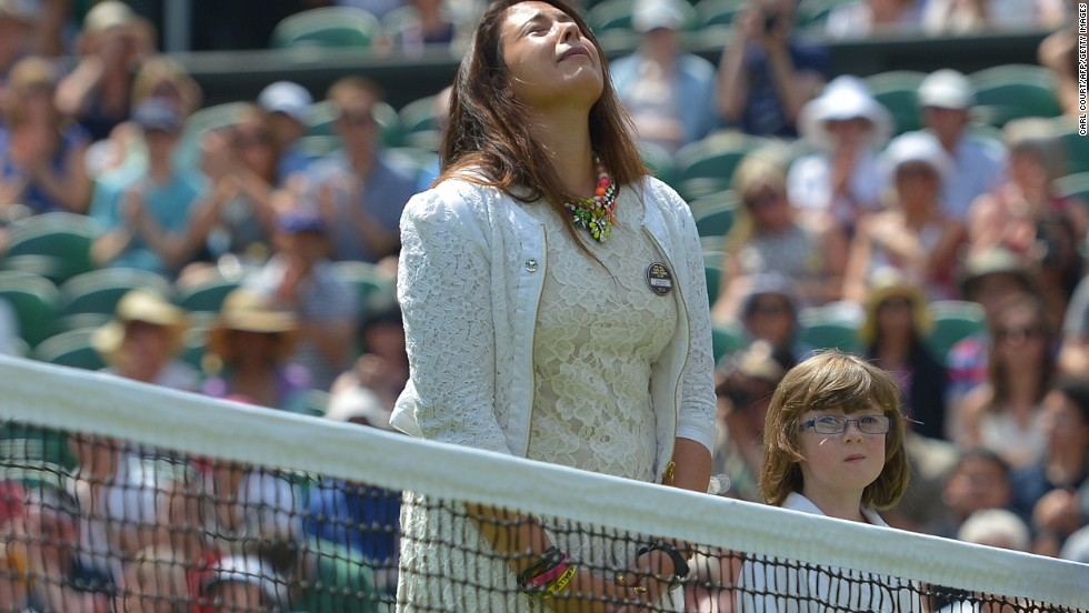 Marion Bartoli, the 2013 Wimbledon women's singles champion, takes part in an emotional ceremonial coin toss on Centre Court in honor of former British No. 1 Elena Baltacha who died from cancer at the beginning of May.
