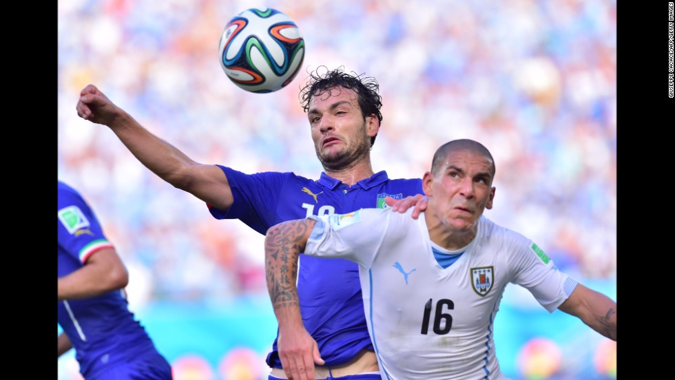 Italy's Marco Parolo, left, and Uruguay's Maximiliano Pereira vie for the ball.