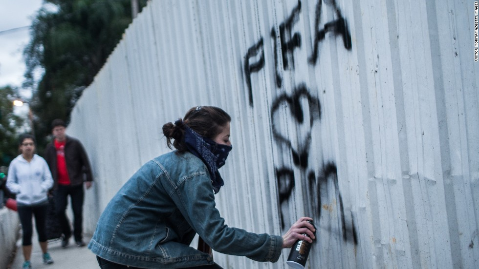 "Anger around the hosting of the World Cup, however, has pushed an increasing number of artists and protesters to ""try to do something with ... a more critical view,"" said Paulo Ito.<br />Here, a member of the MPL 'Free Pass Movement' sprays graffiti during a protest for free transportation."