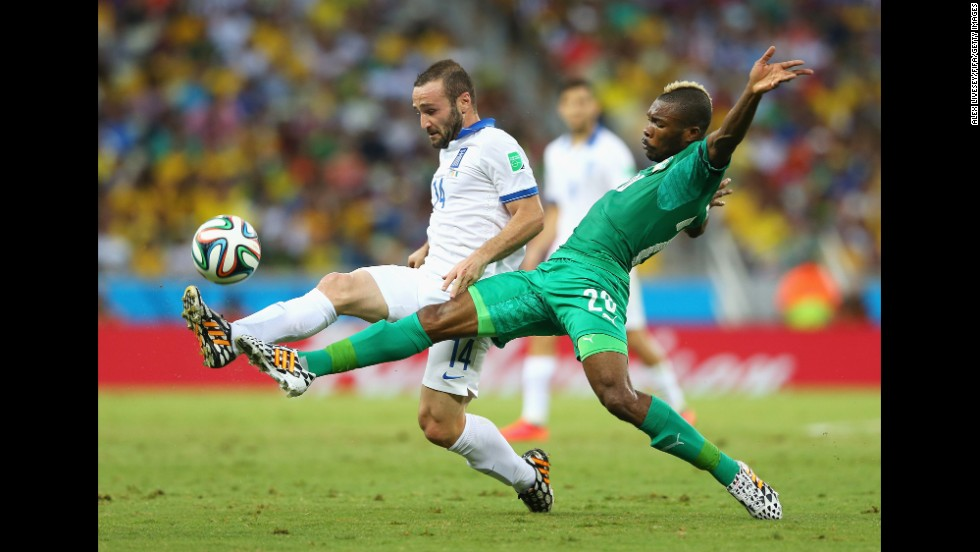 Dimitris Salpingidis of Greece, left, and Die Serey of the Ivory Coast compete for the ball.