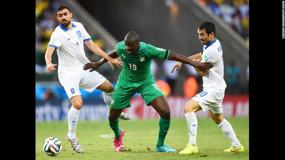 Yaya Toure of the Ivory Coast is challenged by Giannis Maniatis, left, and Giorgos Karagounis of Greece.