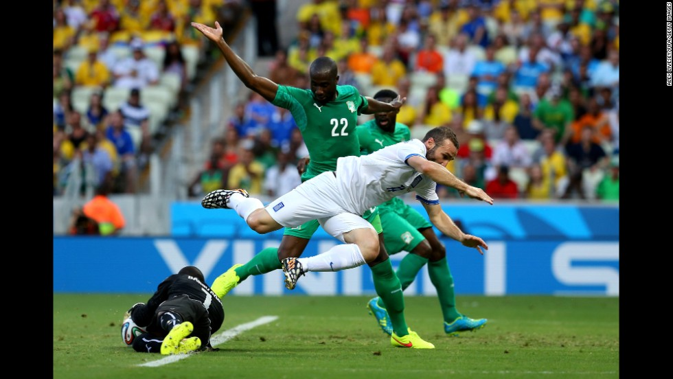 Boubacar Barry of the Ivory Coast makes a save while Dimitris Salpingidis of Greece tries to take a shot.