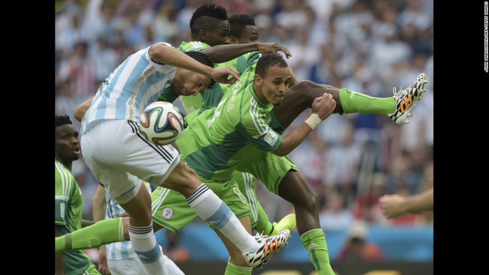 Argentina's defender Ezequiel Garay, left, and Nigeria's forward Peter Odemwingie, center, jump to head the ball, during a match between Nigeria and Argentina at the Beira-Rio Stadium in Porto Alegre.