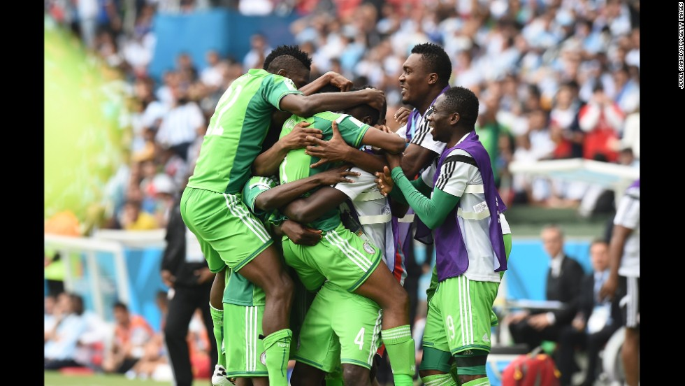 Nigeria's forward Ahmed Musa is mobbed by teammates as he celebrates scoring.