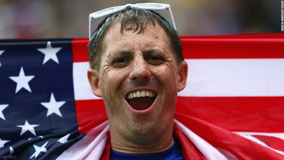 A fan looks on in the rain during the World Cup match between the United States and Germany in Recife, Brazil.