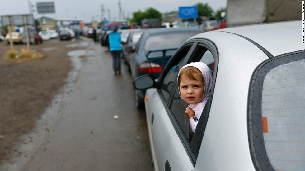 A child looks out from a car in line to leave Ukraine at a border post in Izvaryne along the Russian border on Friday, June 20.