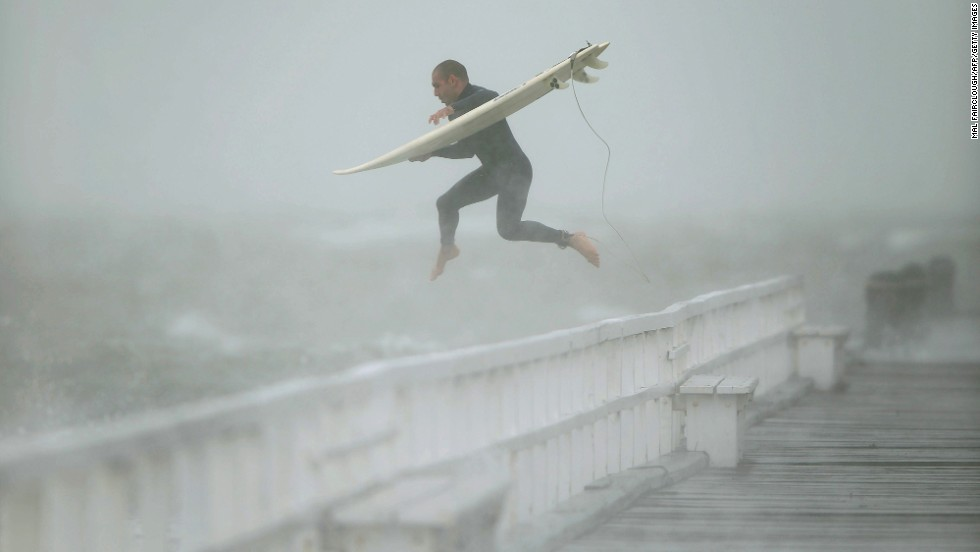 A surfer jumps off the pier into Port Phillip Bay to take advantage of the waves as a storm lashes Melbourne, Australia, on Tuesday, June 24.