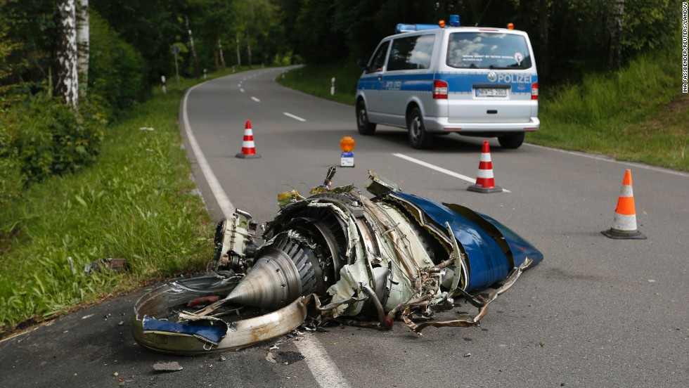 Aircraft parts lie in the street after a midair collision between two planes in Elpe, Germany, on Monday, June 23. A civilian Learjet crashed after colliding with a German military aircraft, which was able to land safely.