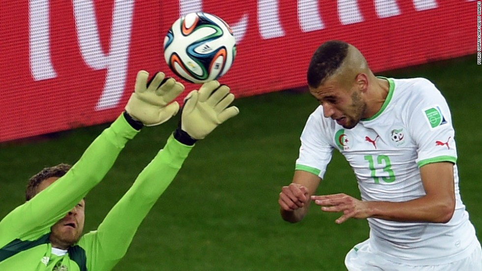 Algeria forward Islam Slimani, right,  heads the ball to score a goal past Russia's goalkeeper Igor Akinfeev during a World Cup match at the Baixada Arena in Curitiba, Brazil.