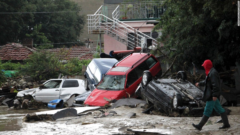 A man walks past damaged cars after heavy flooding in Varna, Bulgaria, on Friday, June 20. At least 11 people died as a result of massive flash flooding and landslides, authorities said.
