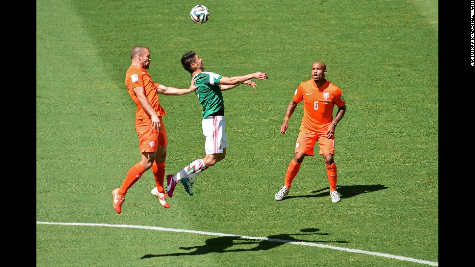 Mexico's Hector Moreno, center, is challenged by Ron Vlaar, left, and Nigel de Jong of the Netherlands.