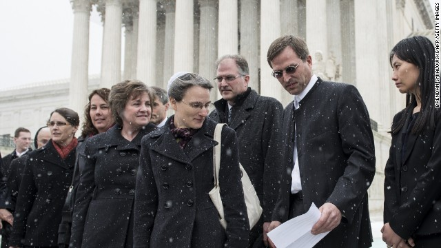 Carolyn Hahn, center, watches as husband Anthony prepares to talk to reporters outside the U.S. Supreme Court on March 25.