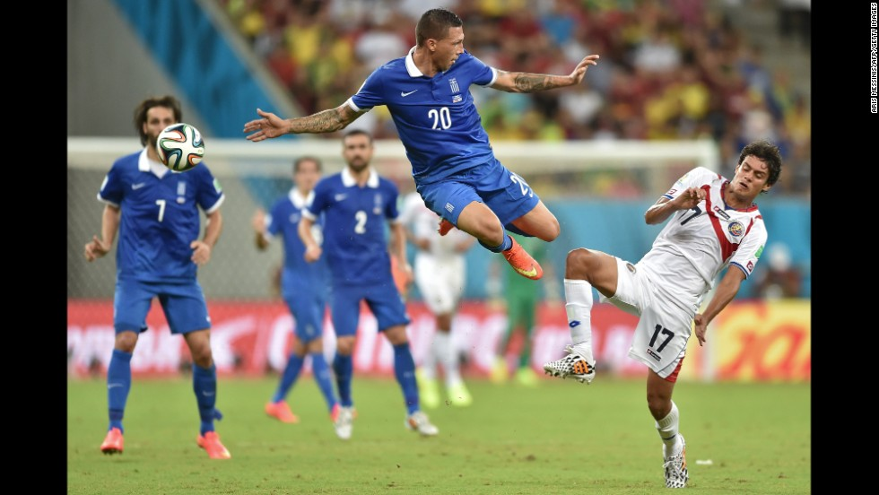 Jose Holebas of Greece, left, vies with Yeltsin Tejeda of Costa Rica for the ball.