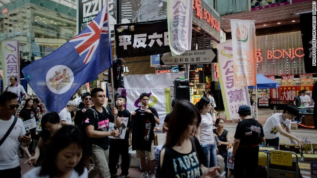A man carries a Hong Kong colonial flag as part of the commemoration of China's 1989 Tiananmen Square military crackdown on pro-democracy protesters, in Hong Kong on June 4, 2014.