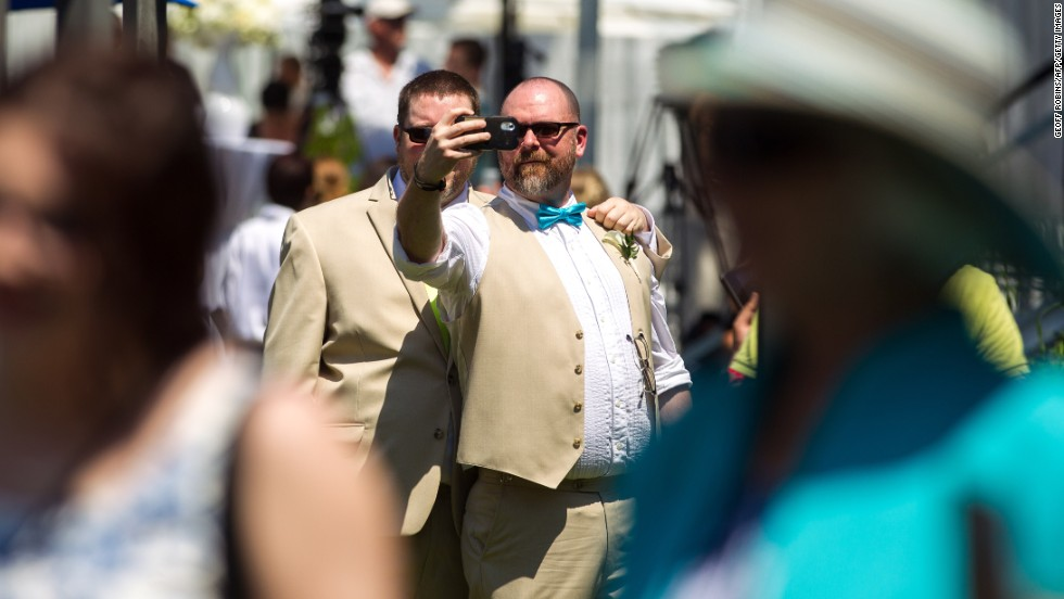 A couple poses for a selfie during the Grand Pride Wedding, a mass same-sex wedding in Toronto on Thursday, June 26. More than 100 couples tied the knot as part of the WorldPride festival running in the city.