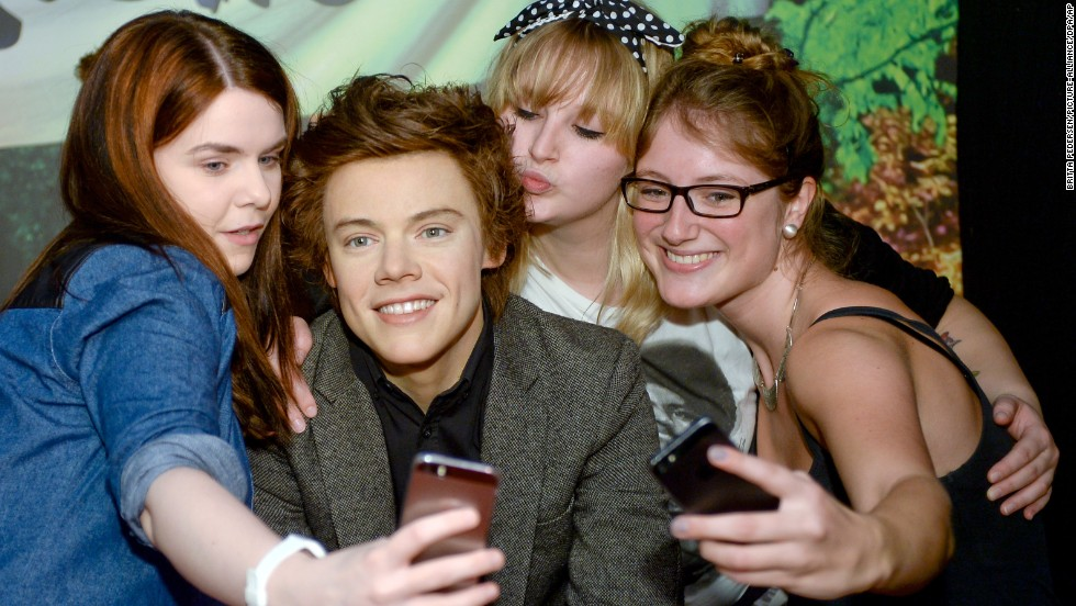 Fans of the boy band One Direction take a selfie with a Harry Styles wax figure Wednesday, June 25, at Madame Tussauds in Berlin.